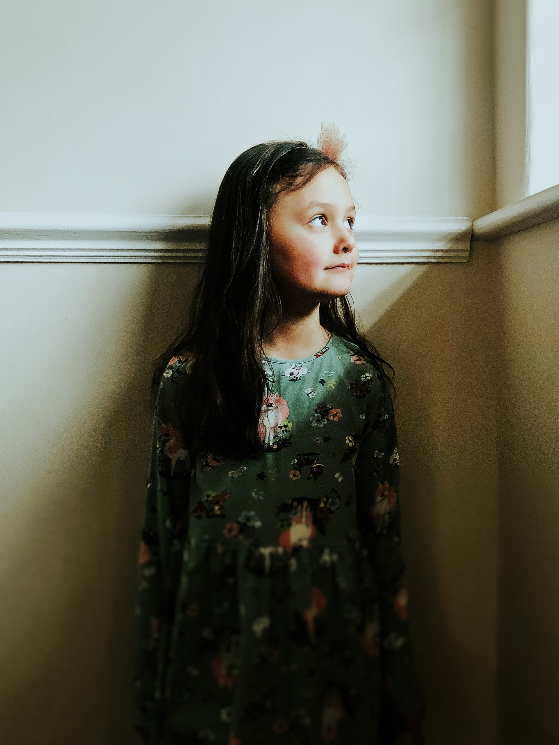 Portrait of a young girl looking out a window